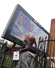 A man walks past an electronic billboard is seen promoting tourism in Lithuania in London, Britain