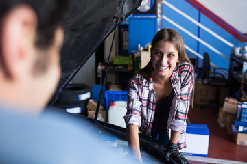 Cheerful young woman working in service station and looking at anonymous man while fixing car engine
