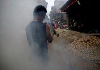 Smoke rise as a man carrying a child walks past the effigy of the demon Ghantakarna during the Ghantakarna festival at the ancient city of Bhaktapur