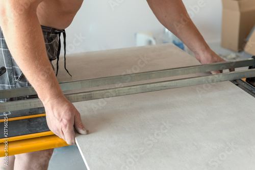 The Man Is Cutting The Floor Tiles Using A Tile Cutter Machine