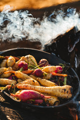 Root vegetables cooking in cast iron over fire
