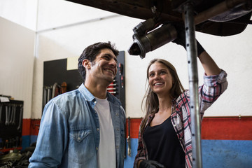 Young woman and man working in team on car repair station standing under car on leveling system and discussing repair