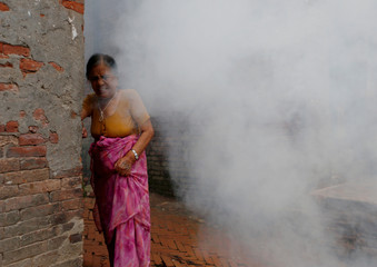 A woman reacts as smoke rise from the burning effigy of the demon Ghantakarna, that was burnt to symbolize the destruction of evil and in belief to drive evil spirits and ghost, during the Ghantakarna festival at the ancient city of Bhaktapur