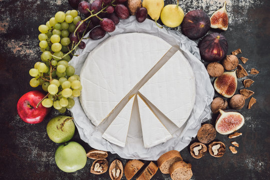 top view of brie cheese, hazelnuts and fruits arranged on dark surface