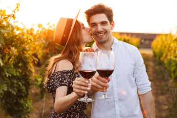 Cute happy loving couple outdoors drinking wine looking camera.