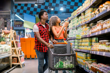 African young Couple with shopping trolley shopping in supermarket grocery aisle