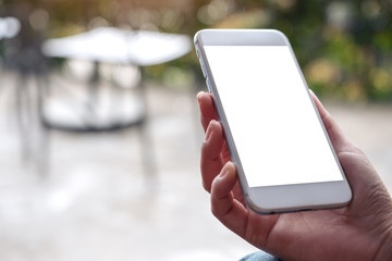 Mockup image of hands holding white mobile phone with blank desktop screen and blur background