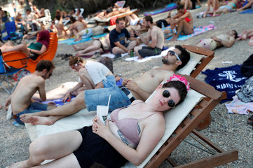 Festivalgoers rest in the shadow during the Sziget music festival on an island in Budapest