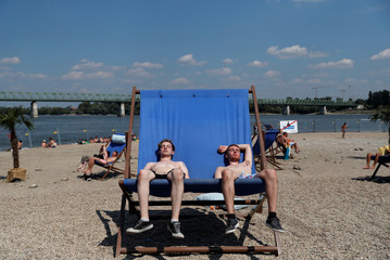 Festivalgoers sunbath during the Sziget music festival on an island in Budapest