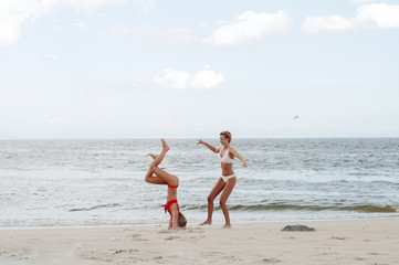 Happiness moment. Two attractive women in bikini on the beach.