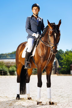 Promising horseman. Young promising horseman feeling excited while preparing for important competition
