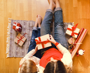 Cheerful mom and her cute daughter girl exchanging Christmas gifts