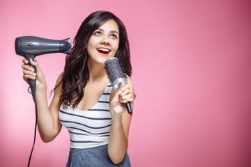 Beautiful young woman feeling happy and singing while using a hairdryer and a hairbrush on pink background