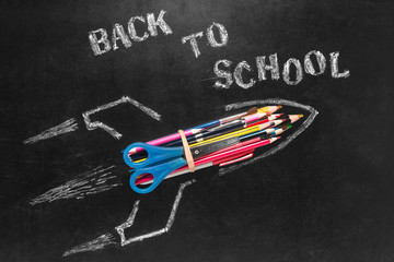 Back to school background. Rocket launch with school supplies on blackboard background with copy space.