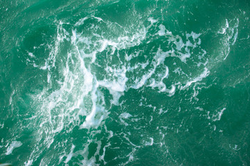 surface of turquoise ocean water with white foam, background, texture
