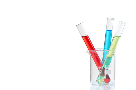 Couloured Laboratory tubes with blue ,red, yellow,liquid in measuring beaker with reflection isolated on white
