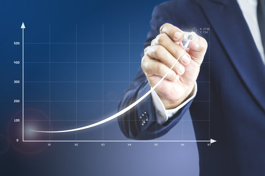 Businessman drawing an exponential curve of a progress in business performance, return on investment - ROI, on a virtual screen presentation.
