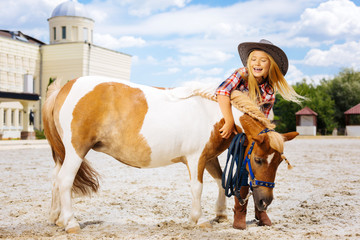 Fun with pony. Amused cowboy girl feeling very memorable and cheerful while having fun with pony...