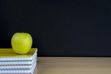 manzana sobre los  cuadenos y pizarra vacía, regreso a la escuela