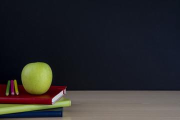 manzana en libros con lápices y pizarra vacía, regreso a la escuela