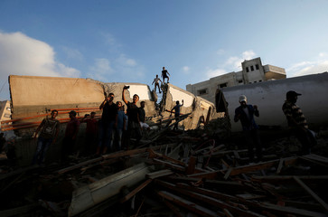 Palestinians take pictures of the remains of a building after it was bombed by an Israeli aircraft, in Gaza City