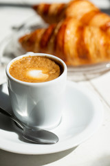 Hot coffee and croissant breakfast in a sunny morning, natural light.