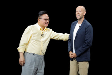 DJ Koh, Samsung's Mobile Communications Division President and CEO greets Spotify CEO Daniel Ek on stage during a Samsung product launch event in Brooklyn