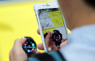 A man uses an Apple iPhone with a cracked screen to photograph the news Samsung Galaxy Watch during a Samsung product launch event in Brooklyn