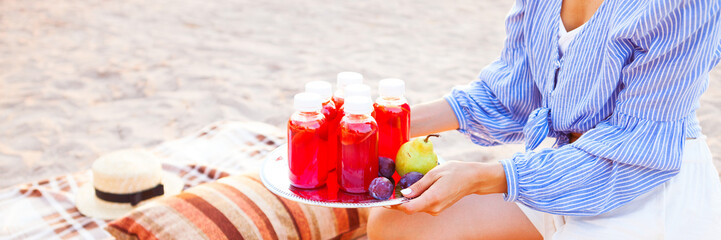 Happy woman holds a dish with a drinks red juice at sunset. Picnic theme on the beach