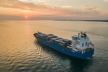 Aerial view of container ship sailing in sea at sunset