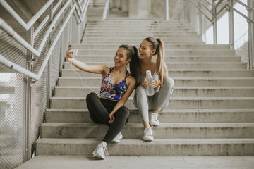 Two athlete women resting and taking selfie after jogging