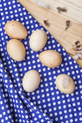 Organic brown eggs from free range chickens on a wooden table with feathers