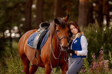 Young woman rider equestrian stands next to brown horse in forest.