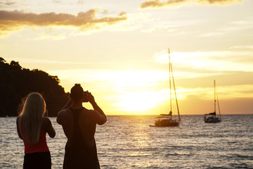 a couple stand watch sunset take photo by the beach