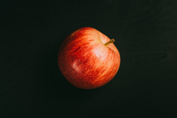 Apple lying on black table in background with blank space as flat lay