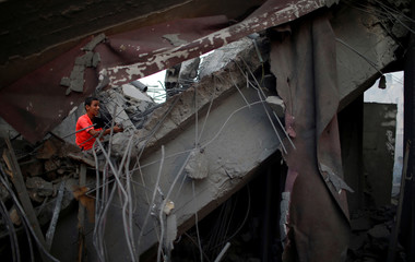 Palestinian boy is seen on the remains of a building after it was bombed by an Israeli aircraft, in Gaza City