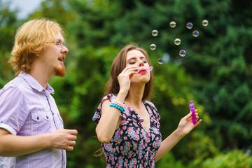 Couple blowing soap bubbles, having fun