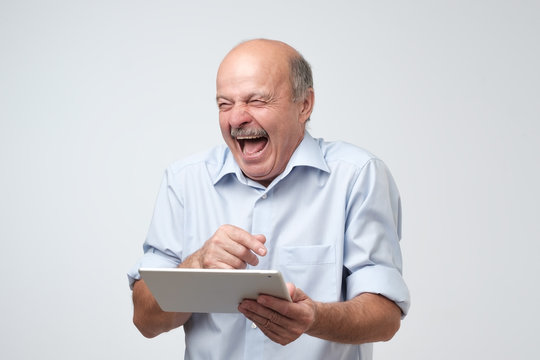 Cheerful mature european man laughing holding tablet