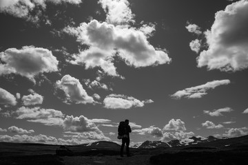 Hiker standing below dramatic clouds
