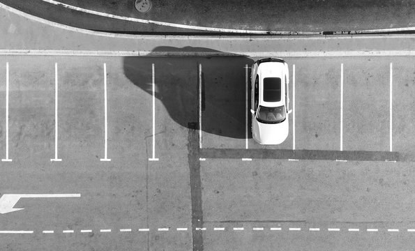Empty parking lots, top view. Aerial view of a car parked alone in a parking, free lots. Black and white photo