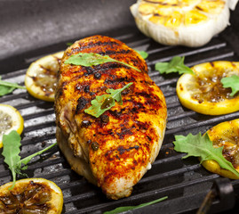 Grilled chicken fillet with spices and fresh vegetables in a pan on black background