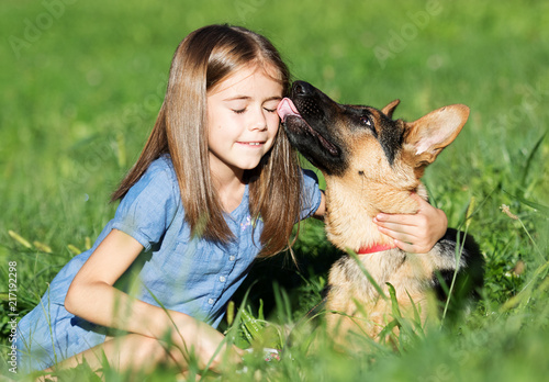 Puppy Kissing Girl In The Grass Stock Photo And Royalty Free Images