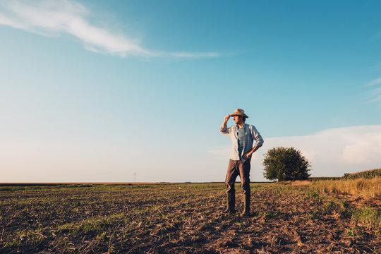Portrait of male farmer standing on bare empty field soil