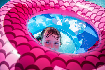 young girl hiding in center of colorful floats in pool