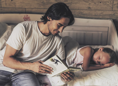 Caring Father Reading Book to Small Daughter.