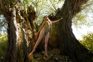 A semi-nude woman poses inside a large  hollow oak tree. She is dressed only with rags and wears  a thorn wreath and veil on her head. She believes the tree is a church. The woman is seen semi-nude.