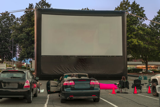 Spectators for car parking with cars, an inflatable screen of the summer cinema, waiting for a movie