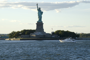 Statue of Liberty and a boat crossing the bay, New York