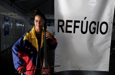 Dulce from Venezuela poses with her instrument after she obtained a refugee status, through the Federal Police and the United Nations High Commissioner for Refugees (UNHCR) at the Pacaraima border control