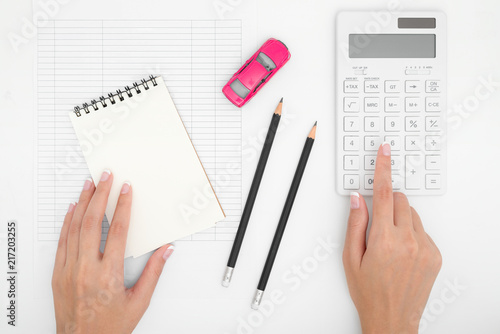 woman hand calculating car expenses payments costs with paper notes